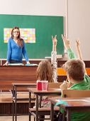 Children In Elementary School Are Raised Hand In Classroom