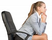 Businesswoman on office chair, with head reclined upon her hands