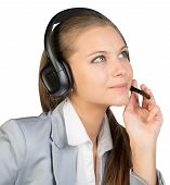 Businesswoman in headset, with her fingers on microphone boom