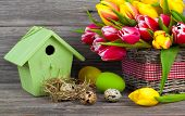 Easter Decoration With Eggs, Birdhouse And Tulips. Wooden Background