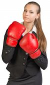 Businesswoman wearing boxing gloves, giving tough look at camera