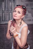 foto of gothic hair  - Beautiful steampunk woman in corset with pink hair praying - JPG