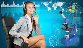 Businesswoman in headset, atom model and microscope