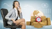 Businesswoman in headset, sitting on office chair. Globe, commodity boxes and alarm-clock beside