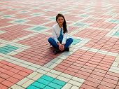 Photo of smiling woman sitting on the paving slab