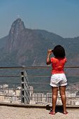 Woman with red shirt photographing Christ the Redeemer