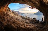 stock photo of cave woman  - Young woman lead climbing in cave with beautiful view in background - JPG