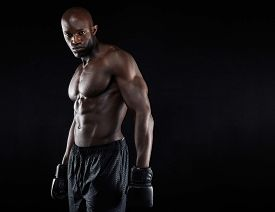 image of boxers  - Portrait of muscular male boxer with boxing gloves against black background - JPG