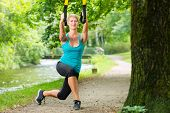 stock photo of suspension  - Young woman exercising with suspension trainer sling in City Park under summer trees for sport fitness - JPG
