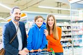 stock photo of grocery cart  - Family with shopping cart in grocery store - JPG