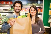 foto of supermarket  - Smiling couple holding a shopping bag full of food in a supermarket - JPG