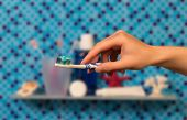 picture of toothbrush  - Hand taking Toothbrush from bathroom shelf on blue background - JPG