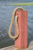 picture of bollard  - Red Wooden Boat Bollard And Rope at Dock - JPG
