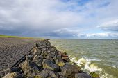 stock photo of dike  - Deteriorating weather over a dike along a sea in spring - JPG
