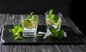 picture of mojito  - Two glasses of mojito cocktail on a black slate board with copy space for text - JPG