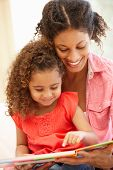 picture of mixed race  - Mixed race woman and daughter reading - JPG