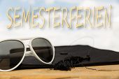 stock photo of spring break  - sunny background with mortarboard sun glasses and the german word for spring break - JPG