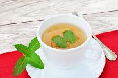pic of mint leaf  - Cup of mint tea with mint leaves on red table cloth over wooden table - JPG
