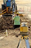 pic of street-rod  - Construction excavation contractor uses a level rod and laser to dig a trench for a concrete fondation wall - JPG