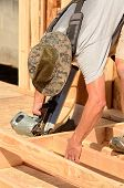 stock photo of top-gun  - Building contractor worker using a air nail gun to attach studs to the top and base plate of the wall for the first floor on a new home construciton project - JPG