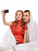 stock photo of two women taking cell phone  - A pregnant woman and her husband are photographing themselves on the cell phone on white back - JPG