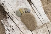 image of arch foot  - Photograph of beach stones arranged to form foot print - JPG