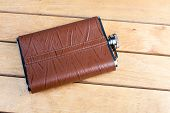 foto of flask  - Brown hip flask on the wooden table  - JPG