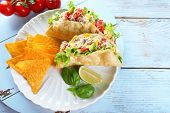 image of tacos  - Tasty taco with nachos chips and vegetables on plate on table close up - JPG
