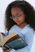 stock photo of girl reading book  - Beautiful Six Year Old In Glasses Readign Large Book - JPG