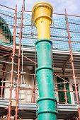 stock photo of scaffold  - Scaffolding construction with slide for debris - JPG