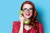 foto of redhead  - Smiling redhead girl in red polka dot dress with green dial phone on blue background - JPG