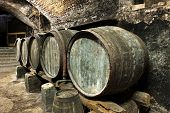stock photo of keg  - Five Old and Weathered Keg Barrels Stacked in Row Along Wall in Old Stone Wine Cellar - JPG