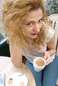 stock photo of prone  - young blonde woman drinking coffee sitting on the chair with prone and cookie on the table - JPG