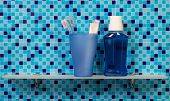 stock photo of toothbrush  - Toothpaste and toothbrushes on bathroom shelf and blue background - JPG