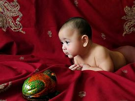 stock photo of baby frog  - Baby boy lies on the Indian silver embroidered dark - JPG