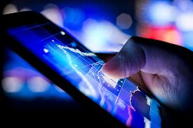 stock photo of check  - A person checking stock market data on a mobile device - JPG