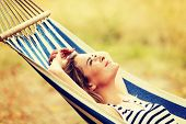 Young blonde woman resting on hammock poster