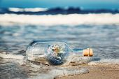 Earth in the bottle coming with wave from ocean. Concept of environment, nature care, save clean wor poster