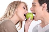 Portrait of a man and a woman eating an apple