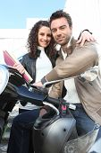 Portrait of a smiling couple near a motorcycle