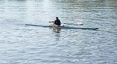 one single sculler / rower / oarsman on a river or lake rows in small sport boat