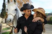Cowboy couple with white horse