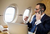 Success Concept. Glad Handsome Male Having Conversation By Cellphone While Sitting In Airplane Seat  poster