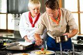 Zwei Köche in Teamwork - Mann und Frau - in ein Restaurant oder Hotel Küche kochen Köstlichkeiten, er