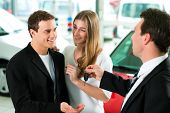 Sales situation in a car dealership, the dealer is handing auto keys to a young couple, they are exc