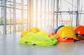 White, Orange, Yellow And Blue Safety Helmet With Reflective Clothing On Desk At Construction Site A poster