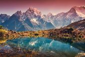 Mountains With Snow Covered Peaks, Red Sky Reflected In Lake poster