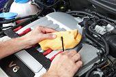 Mecánico con un dip stick comprobar el aceite del motor en un coche deportivo de v6