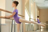 Young Ballerina Practice On Barre. Girl Stretching Out On Railing At Ballet Studio. Exercises Of Bal poster