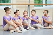 Young Beautiful Ballerinas Talking In Ballet Studio. Group Of Little Ballet Dancers Sitting On The F poster